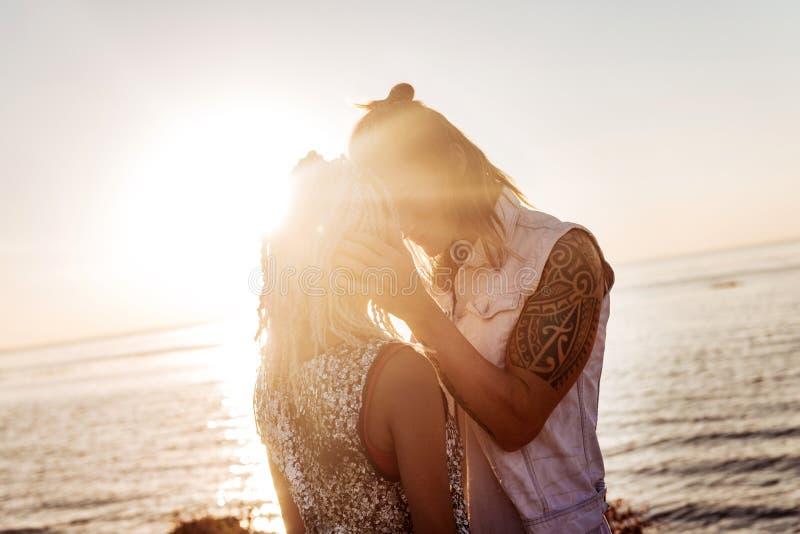 Hombre de amor que cuida con el tatuaje que besa a su novia con los dreadlocks fotografía de archivo libre de regalías