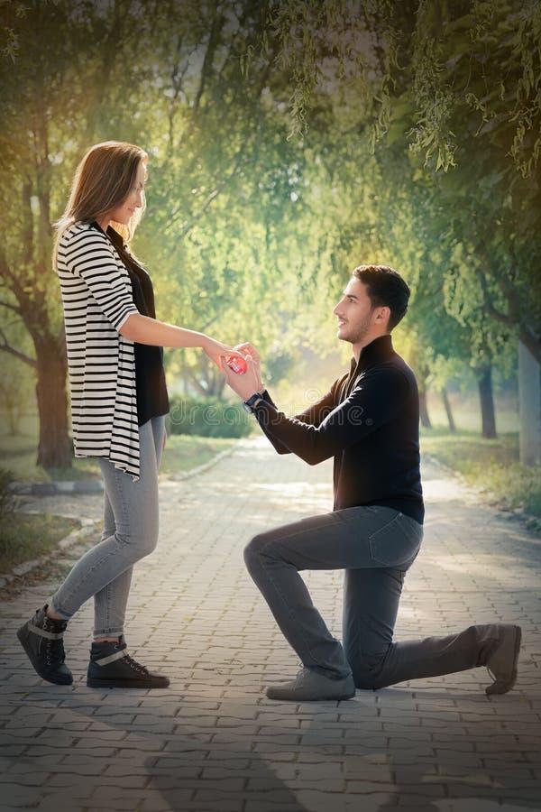 Hombre de arrodillamiento que propone con un anillo de compromiso imagen de archivo libre de regalías