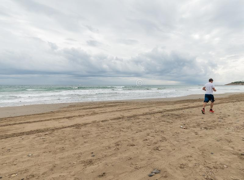 Hombre de Atlethic que corre en la playa fotos de archivo