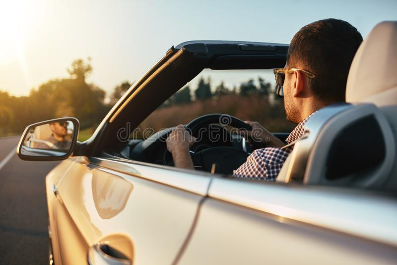 Hombre de Aucasian que conduce cabrio en verano imagenes de archivo