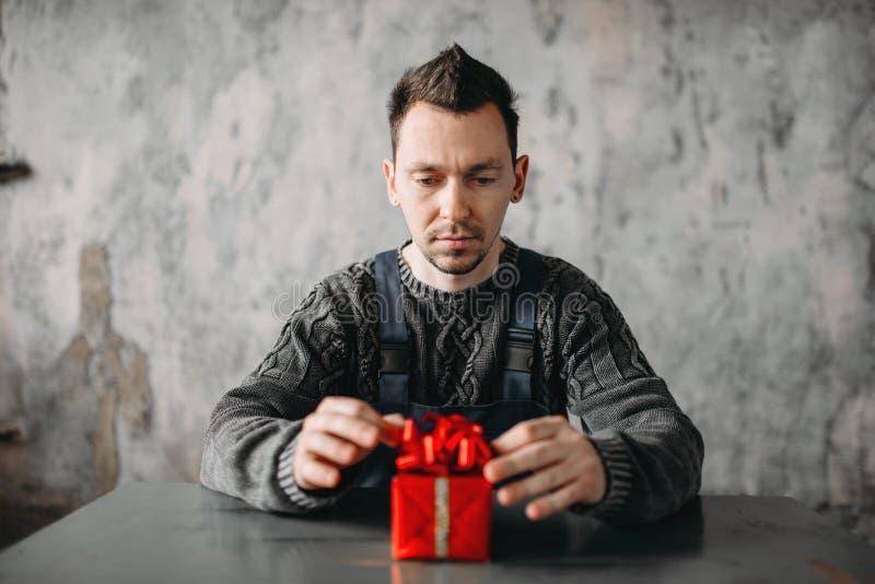 Hombre de Autist que se sienta contra el regalo en papel de embalaje fotos de archivo libres de regalías