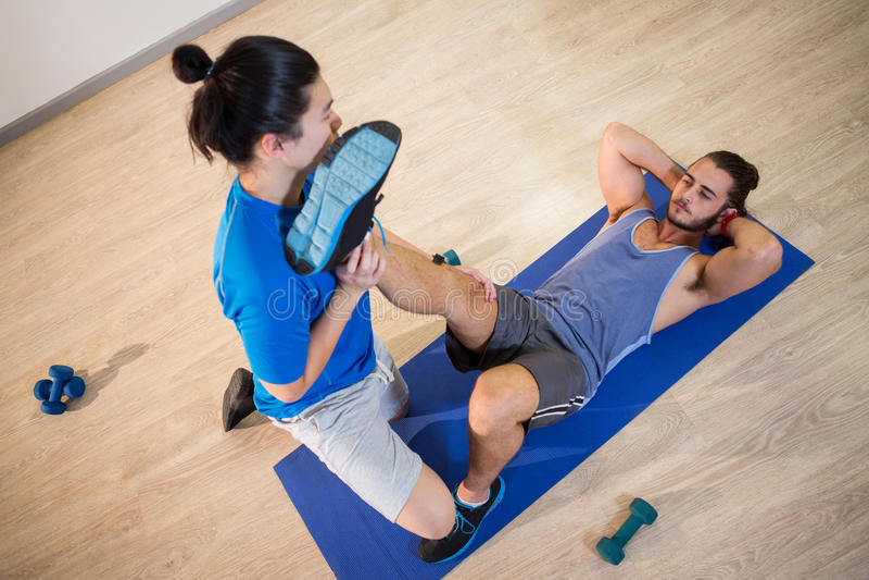 Hombre de ayuda de la aptitud del instructor de la yoga con las flexiones de la pierna imagen de archivo libre de regalías