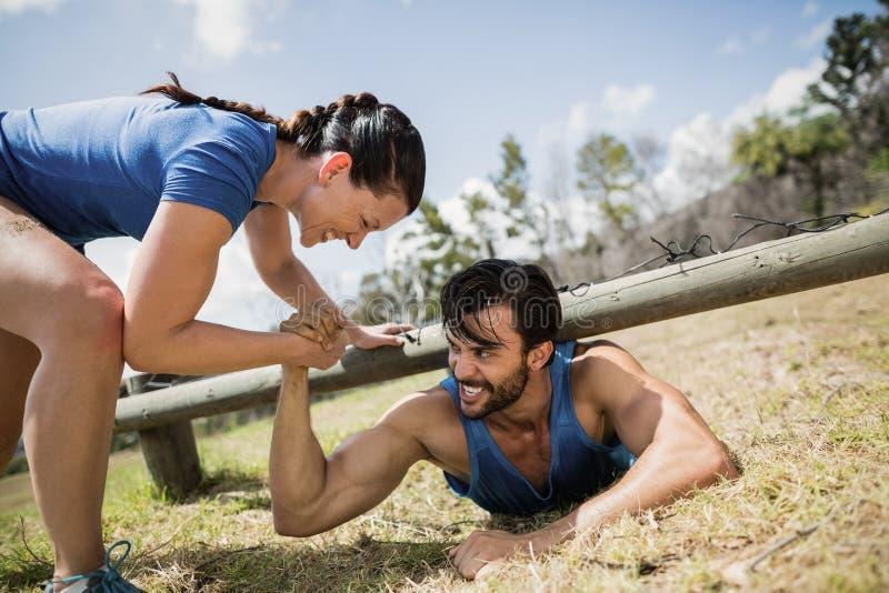 Hombre de ayuda sonriente de la mujer apta que se arrastra bajo red durante carrera de obstáculos imagenes de archivo