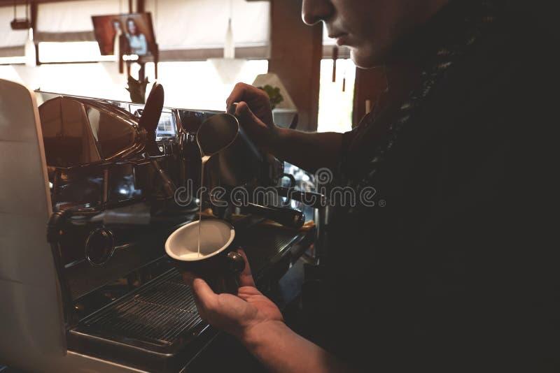 Hombre de Barista que vierte la leche azotada de espumejear la jarra en taza con la situación de la bebida del café cerca del caf imagenes de archivo