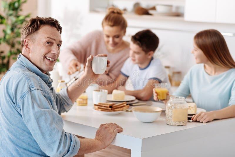 Hombre de Cheeful que desayuna con su familia imágenes de archivo libres de regalías