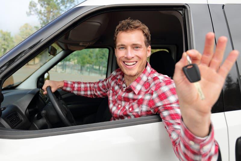 Hombre de conducción feliz que muestra nuevas llaves o alquiler del coche fotos de archivo libres de regalías