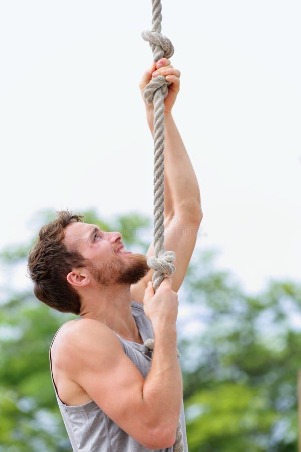 Hombre de Crossfit que hace subir del entrenamiento de la subida de la cuerda foto de archivo libre de regalías