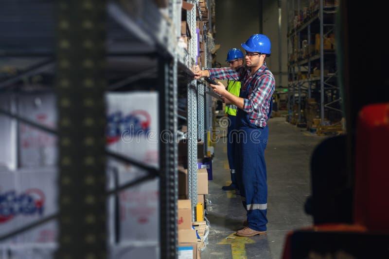 Hombre de dos trabajadores en uniforme delante del estante del almacén foto de archivo