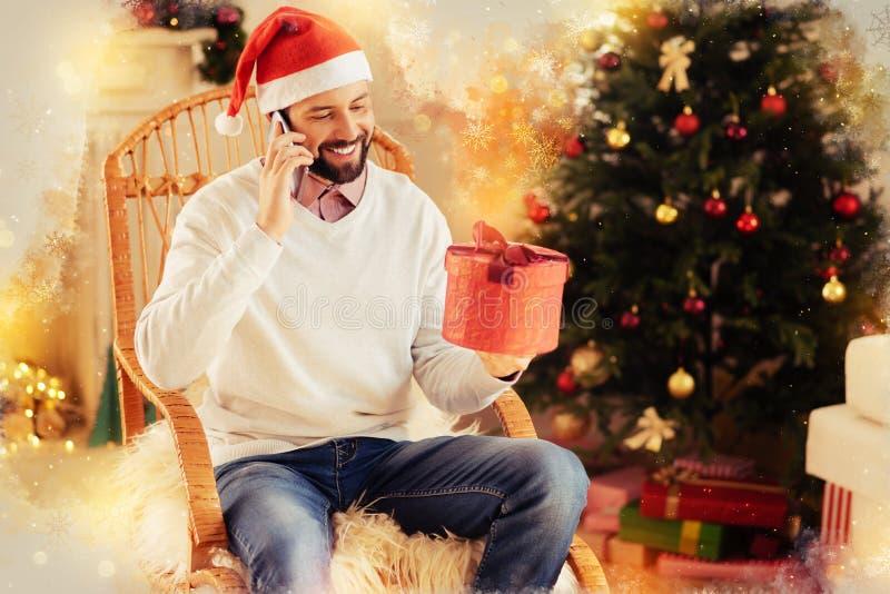 Hombre de emisión barbudo que sostiene la caja de regalo roja agradable para su esposa en la Navidad imagen de archivo