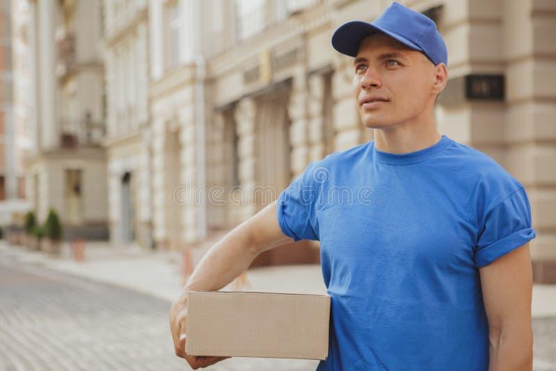 Hombre de entrega alegre joven con la caja de cartón del paquete en las calles de la ciudad fotografía de archivo libre de regalías