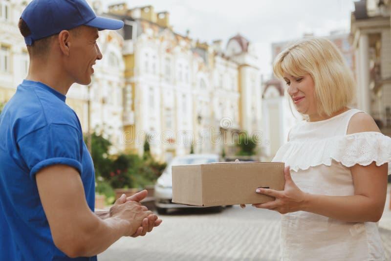 Hombre de entrega alegre joven con la caja de cartón del paquete en las calles de la ciudad fotos de archivo libres de regalías