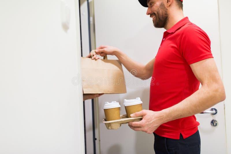 Hombre de entrega con café y comida en el hogar del cliente foto de archivo libre de regalías