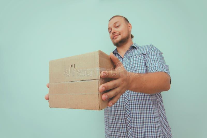 Hombre de entrega con la caja marrón en su puerta casera Fondo azul claro Paquete del control de las manos Servicio de salida fotografía de archivo libre de regalías