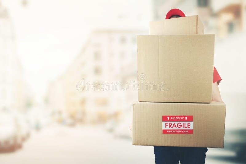 hombre de entrega con la pila de cajas que se colocan en la calle imagen de archivo
