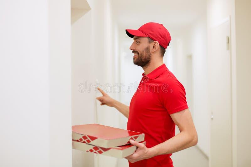 Hombre de entrega con las cajas de la pizza que suenan el timbre imágenes de archivo libres de regalías