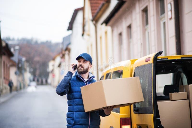 Hombre de entrega con una caja del paquete en la calle imagen de archivo libre de regalías