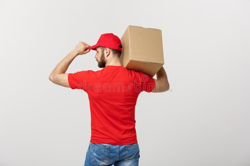 Hombre de entrega del retrato en casquillo con el funcionamiento rojo de la camiseta como el mensajero o distribuidor autorizado  fotos de archivo
