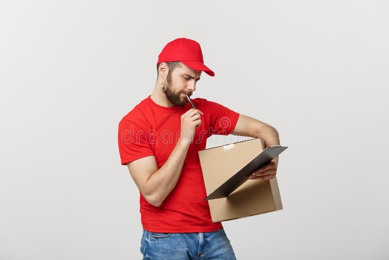 Hombre de entrega del retrato en casquillo con el funcionamiento rojo de la camiseta como el mensajero o distribuidor autorizado  fotografía de archivo libre de regalías