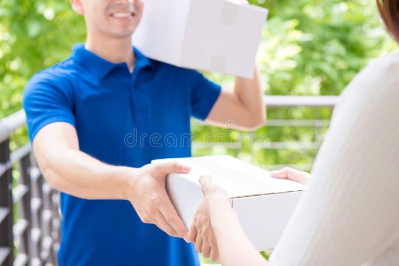 Hombre de entrega en caja de entrega uniforme del paquete del azul a una mujer imagen de archivo