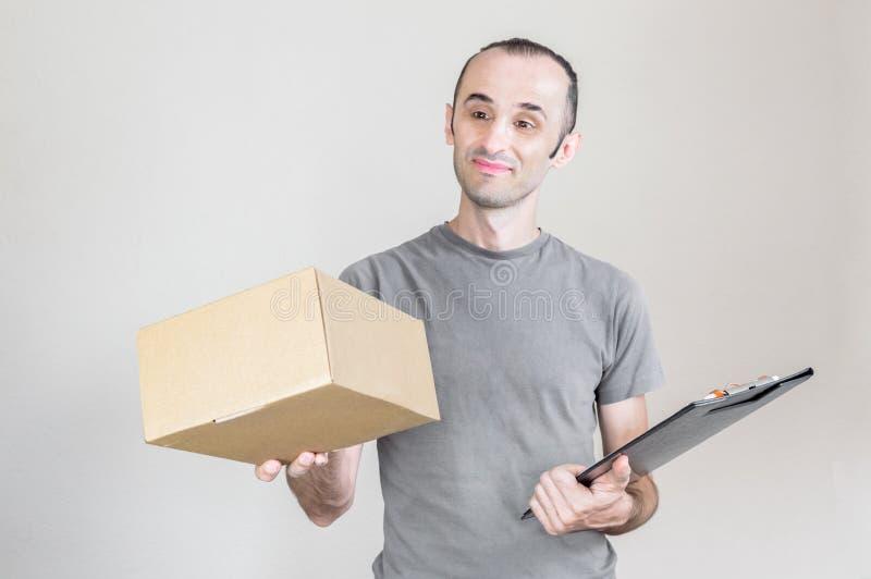 Hombre de entrega feliz con la camiseta gris que lleva una caja del paquete en un fondo blanco imagen de archivo libre de regalías