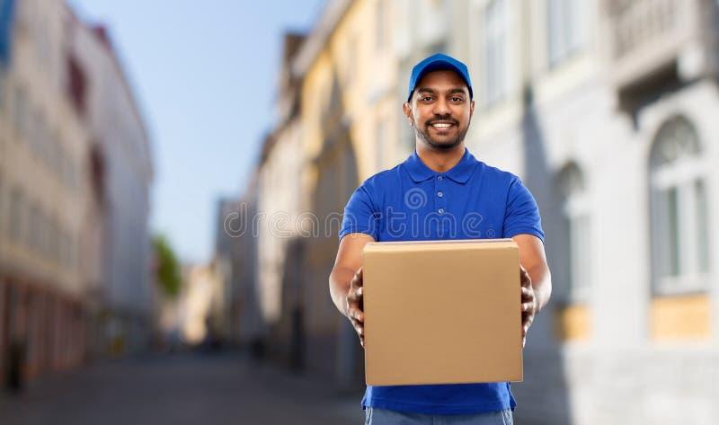 Hombre de entrega indio feliz con la caja del paquete en ciudad imagenes de archivo