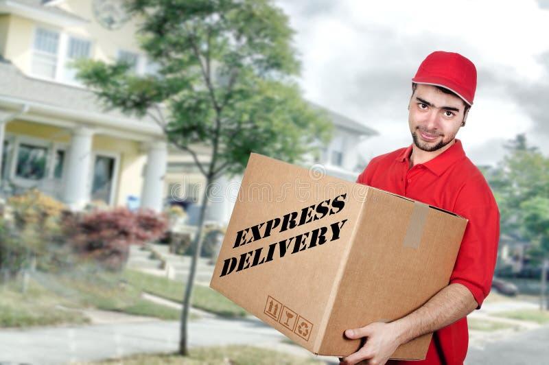 Hombre de entrega en el uniforme del rojo que sostiene la caja imágenes de archivo libres de regalías