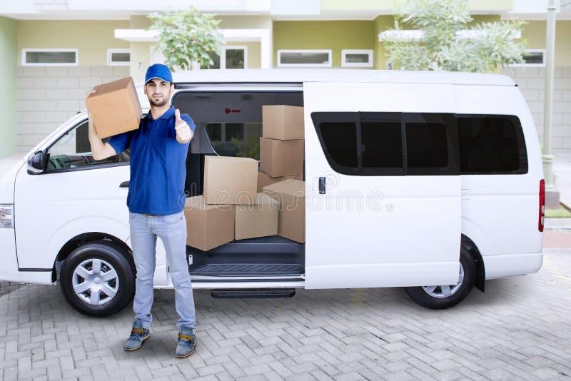 Hombre de entrega joven en Front Van With Cardboard Boxes que muestra los pulgares para arriba foto de archivo