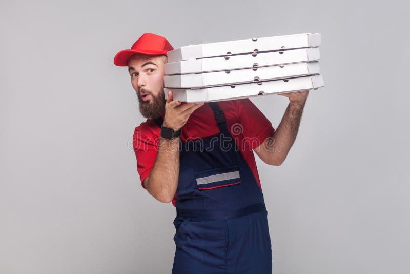 Hombre de entrega juguetón joven con la barba en el t uniforme y rojo del azul imagenes de archivo