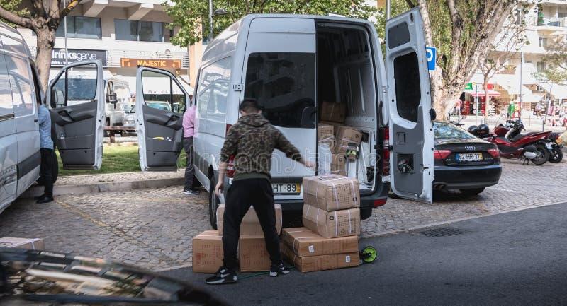 Hombre de entrega que descarga las cajas de su camión en una calle que hace compras de Albufeira, Portugal foto de archivo