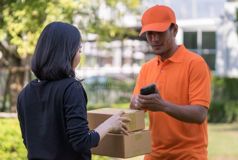 Hombre de entrega que pide que la mujer firme el móvil para la entrega imágenes de archivo libres de regalías