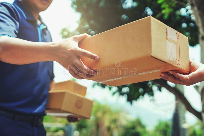 Hombre de entrega que entrega sosteniendo la caja del paquete foto de archivo