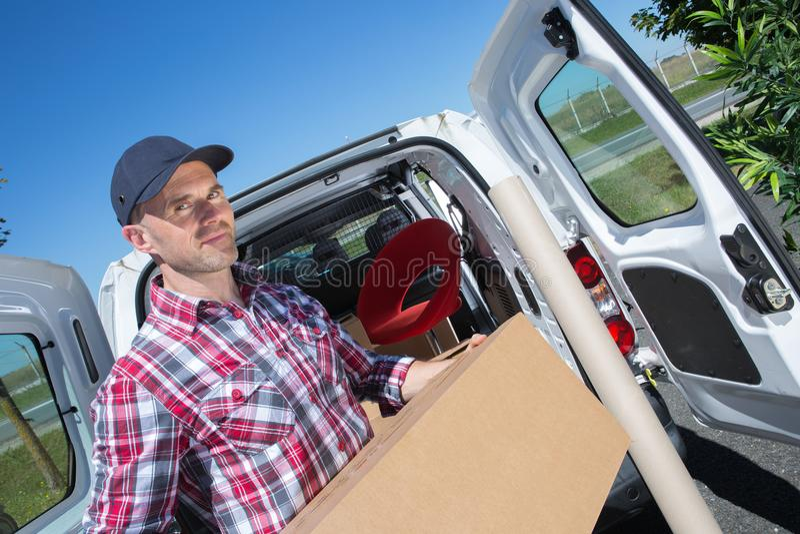 Hombre de entrega que toma el paquete del coche imagen de archivo libre de regalías