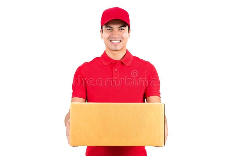 Hombre de entrega sonriente que lleva una caja del paquete imágenes de archivo libres de regalías