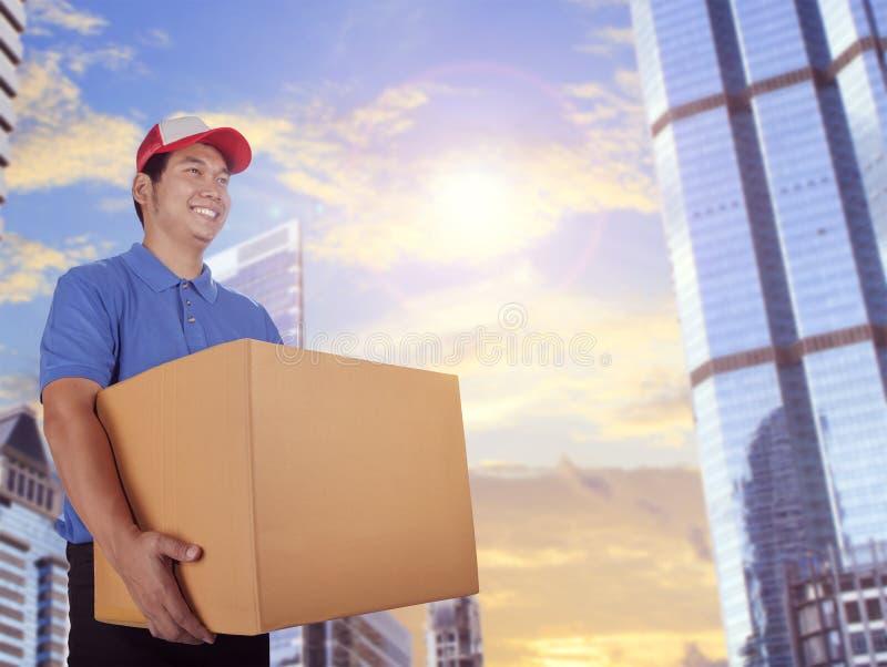 Hombre de entrega y caja de tarjeta que entrega en el edificio de la ciudad fotos de archivo libres de regalías