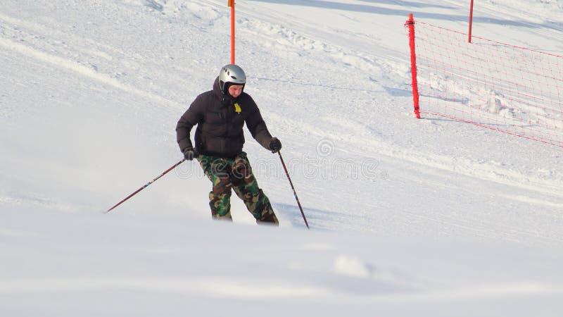 Hombre de esquí secretamente tomado de una colina imagenes de archivo