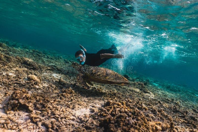 Hombre de Freediver con la tortuga de hawksbill fotos de archivo
