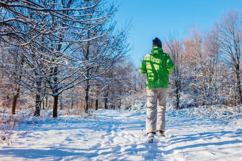 Hombre de funcionamiento del atleta que esprinta en exterior del entrenamiento del bosque del invierno en tiempo nevoso frío Mane foto de archivo libre de regalías