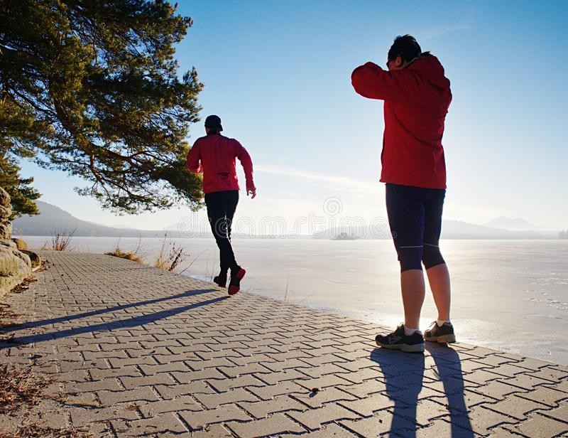Hombre de funcionamiento folowing de la mujer en la playa del lago Equipo de corredores imagen de archivo