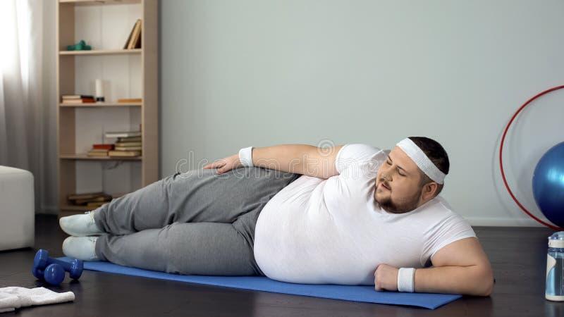 Hombre de gran tamaño que miente en la estera, haciendo ejercicios físicos en casa, peso ardiente fotos de archivo