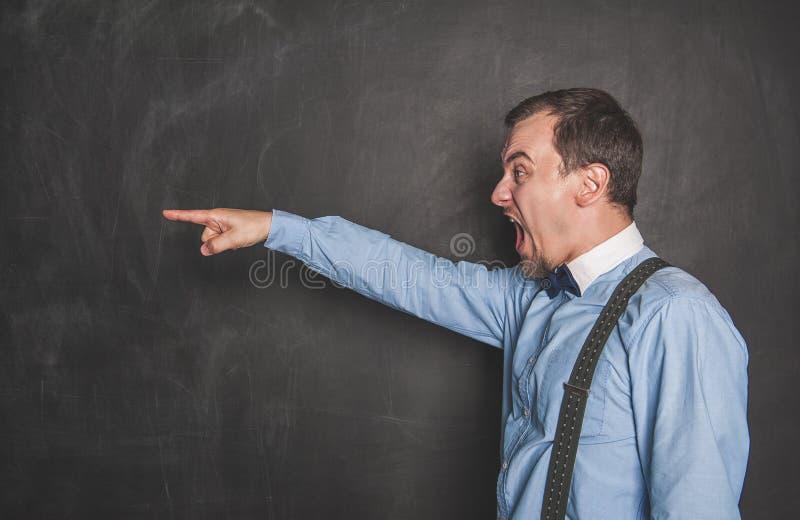 Hombre de griterío enojado del profesor que señala en la pizarra foto de archivo