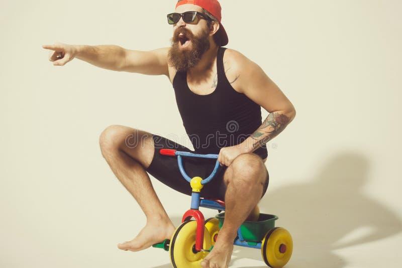 Hombre de grito barbudo en el juguete colorido en gafas de sol, casquillo de la bicicleta imagen de archivo