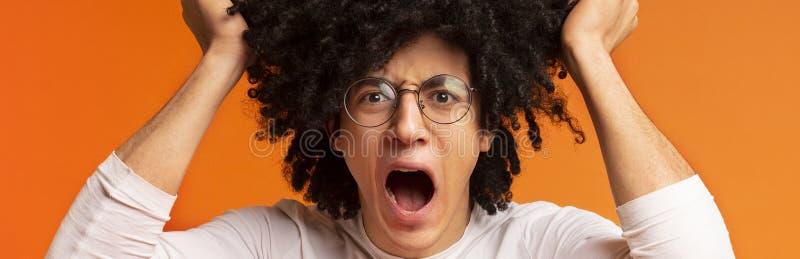 Hombre de grito loco que arranca su pelo espeso en la tensión imagen de archivo libre de regalías