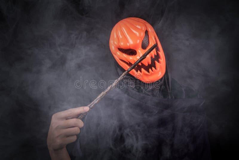 Hombre de Halloween con la máscara de la calabaza que sostiene la vara mágica foto de archivo