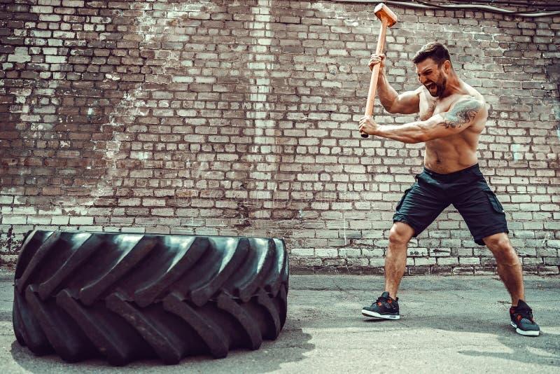Hombre de la aptitud del deporte que golpea el neumático de la rueda con el entrenamiento de Crossfit del trineo del martillo fotos de archivo libres de regalías