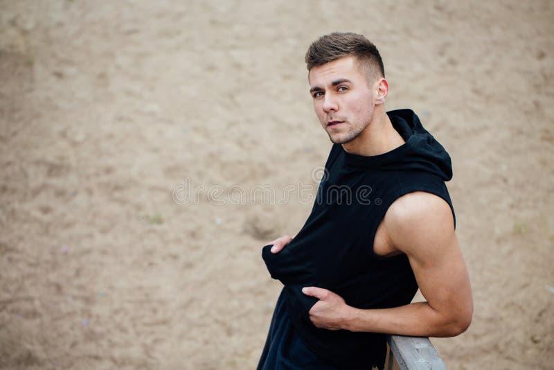 Hombre de la aptitud del deporte que presenta en la playa Parque masculino de la caída del exterior del atleta foto de archivo libre de regalías