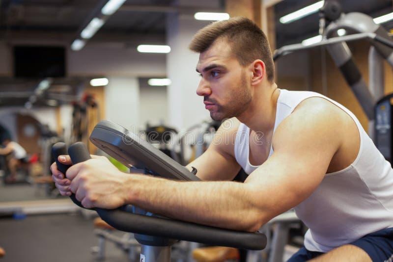 Hombre de la aptitud en la bicicleta que hace el giro en el gimnasio Hombre joven apto que se resuelve en la bici del gimnasio imágenes de archivo libres de regalías