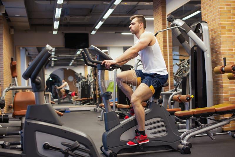 Hombre de la aptitud en la bicicleta que hace el giro en el gimnasio Hombre joven apto que se resuelve en la bici del gimnasio fotografía de archivo