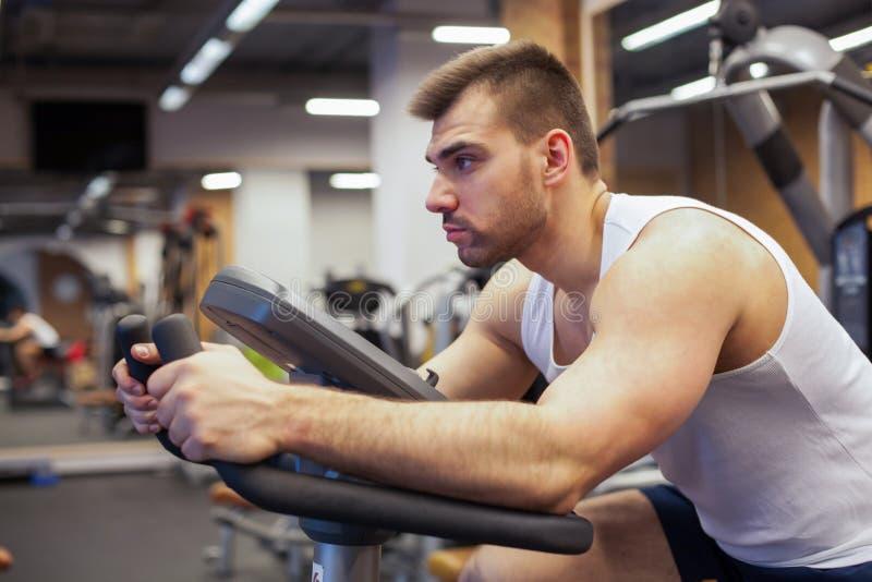 Hombre de la aptitud en la bicicleta que hace el giro en el gimnasio Hombre joven apto que se resuelve en la bici del gimnasio imagenes de archivo