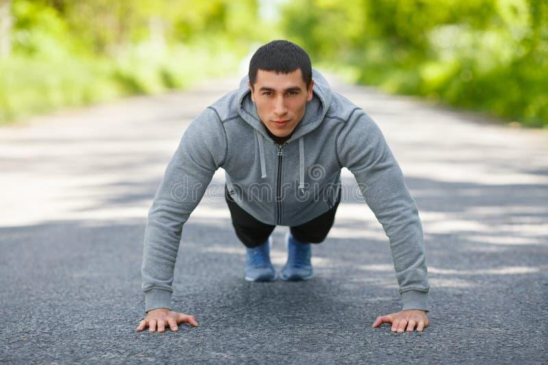 Hombre de la aptitud que ejercita los pectorales, al aire libre Cruz-entrenamiento masculino muscular en parque de la ciudad foto de archivo libre de regalías