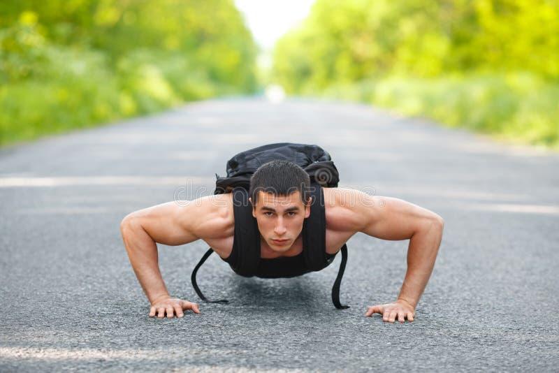 Hombre de la aptitud que ejercita los pectorales, al aire libre Cruz-entrenamiento masculino muscular en parque de la ciudad imágenes de archivo libres de regalías